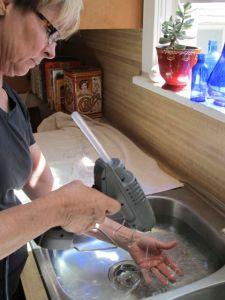 Artist Gerri Sayler standing at kitchen sink creating hot glue installation