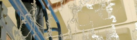 Gerri Sayler working on lift to install hot glue exhibit titled Numinous at Spurgeon Art Gallery