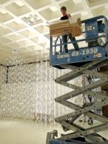 artist Gerri Sayler working on hot glue installation titled Numinous for Spurgeon Art Gallery
