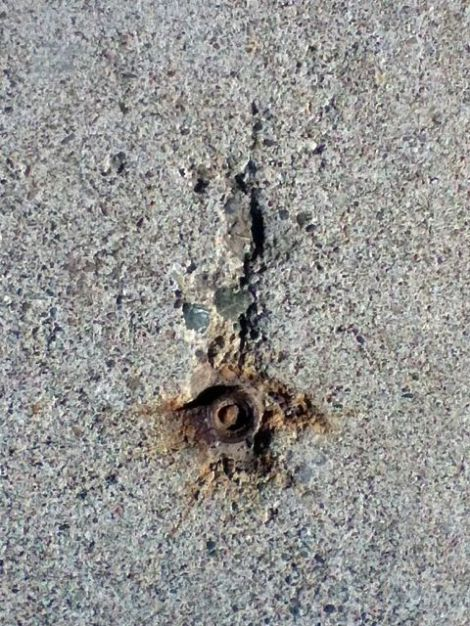 image of sidewalk crack wrapped around a circular metal object