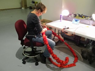 Artist Gerri Sayler working with red satin for Terra Ignis art installation at Nicolaysen Art Museum